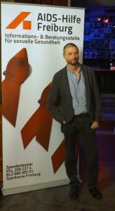 Ralf König vor dem AH-Plakat fotografiert